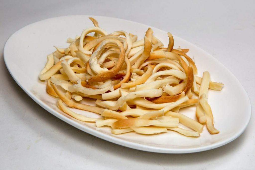 پنیر دودی یا همان پنیر رشته ای که داخل یک بشقاب سفید است. یک غذاب خوب برای بعد از ترک سیگار